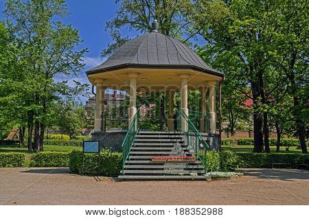 The photo shows the gazebo situated in the city park. Round columns are supported by a domed roof. The stairs lead stone stairs. In front of the gazebo the ground is covered with yellow gravel.