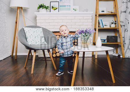 A small child, a boy sits on a wooden floor in a bright room for a year. Dressed in blue jeans and a shirt in a cage. Family concept