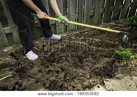 Adult using a hoe to cultivate an urban garden in preparation for spring planting