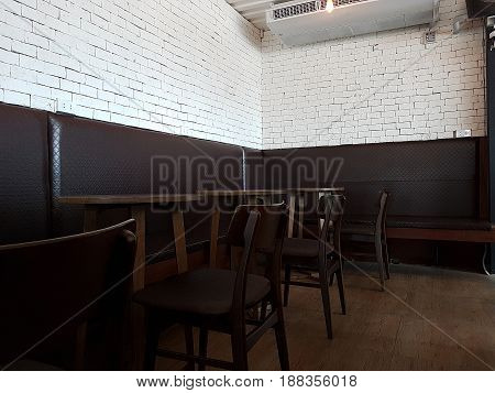 27 May 2017 Pathum Thani ;Thailand : Coffee shop interior with a large sofa near a white wall a row of tables with chairs near windows and a big horizontal poster on the wall.