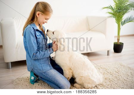 Portrait of a girl playing with her dog