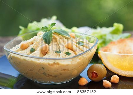 Homemade hummus with chickpeas, olive oil and mint leaf in glass bowl. Closeup of chickpeas and sesame humus.