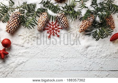 Snowy christmas background with fir branch and pine cones