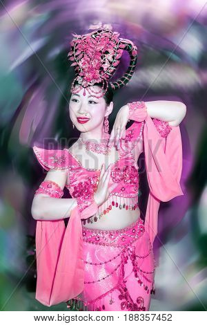 portrait of a beautiful asian girl in a pink stage costume