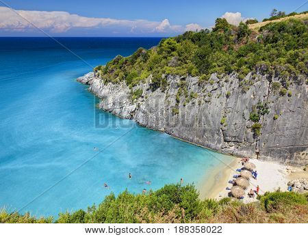 View on Zakynthos Island sand beach around rocks, swimming and toasting people on white sand beach, blue ultramarine water of Ionian Sea. Famous Xigia sand beach. Greece islands holidays tours trips