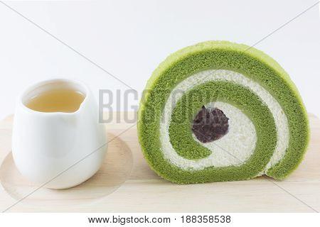 Green tea roll cake on wooden board.