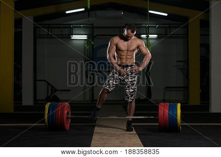 Bodybuilder Performing Back Exercising With Barbell In Gym