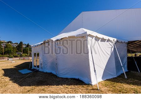 A large white tent in a grass field for parties and entertaining