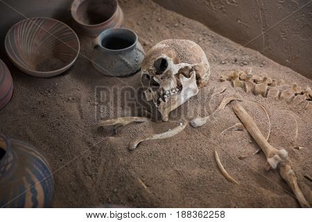 Aged skeleton with pots in his grave closeup