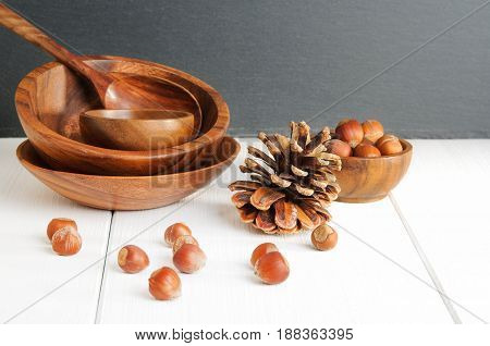 Wooden theme: hazelnuts pinecone utensil on white table
