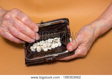 Senior woman sitting on window sill with purse with pills. closeup. Poverty concept. All money was spent for pills