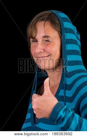 authentic attractive europeen lady, standing relaxed, wearing a blue striped sweater, giving a thumbs up