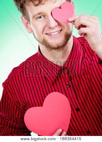 Love and help from people. Charming lovely man with two red paper hearts persuade to be good helpful hopeful. Valentines Day or charity concept.
