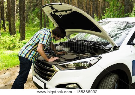 A man looking at the car's engine and learning about the broken ones