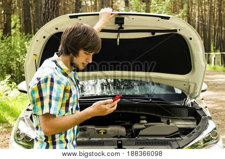 A sad man is waiting for help and calling the support service because his car broke down