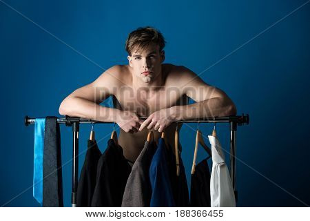 wardrobe. shaved man with naked muscular torso standing at wardrobe hanger with formal outfit of jacket tie shirt and suit on blue background