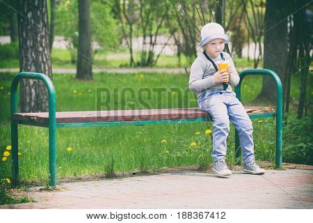 Trendy boy in pajamas sitting on the bench with a cocktail