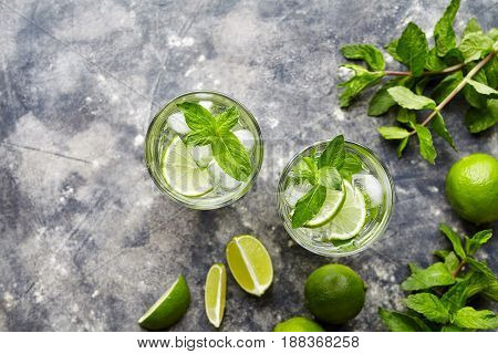 Mojito traditional Cuban cocktail ctail non alcohol drink two highball glass, summer tropical vacation beverage with rum, mint, lime juice, soda water, sugar and ice on concrete background. Top view