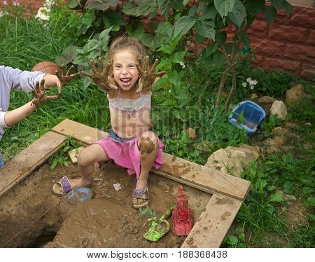 little girl playing with toys in a sandbox with good emotion.
