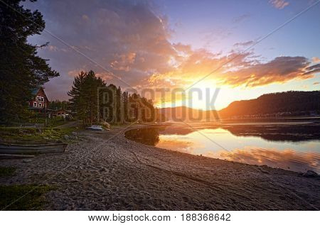 Beautiful summer sunset on the lake. Sun's rays Shine through the trees in the evening on the lake. Camping coastline