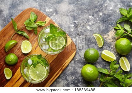 Mojito cocktail non alcohol bar drink top view copy space two highball glass on wooden cutting board, summer tropical vacation beverage with rum, mint, lime, soda water and ice on concrete table.