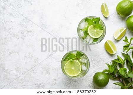 Mojito cocktail alcohol bar long drink traditional fresh tropical beverage top view copy space two highball glass, with rum, spearmint, lime juice, soda water and ice on white concrete table.