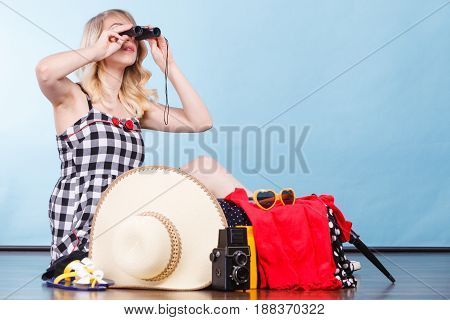 Packing for journay traveling concept. Woman looking through binoculars sitting on floor with suitcase and full of things ready to be taken on summer holiday.