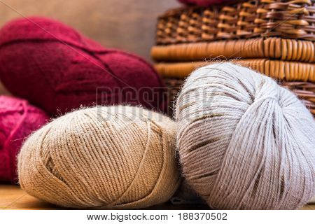 Clews balls of natural red beige grey wool yarn wicker crafts basket cozy atmosphere authentic style close up