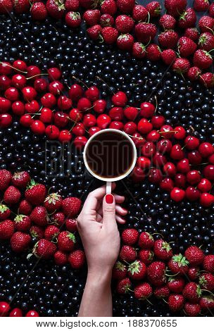Hello summer harvest. A cup of black coffee in a female hand on a black background with summer berries: strawberries, currants, cherries. The concept of the arrival of summer mood and heat. Flat lay