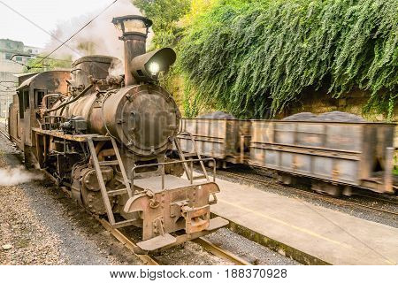 Steam narrow-gauge locomotive and moving freight train with coal. Yuejin. Sichuan province. China.