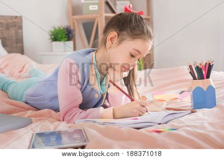 Young teenager girl alone at home childhood doing homework