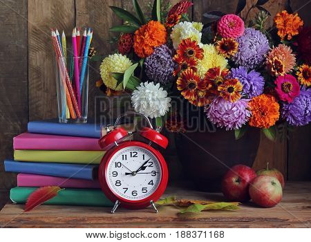 Back to school. Alarm clock bouquet apples and books on the table. The teacher's day. The day of knowledge. September 1.