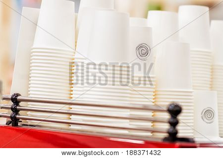 Rows of upside down white cups of cardboard, paper for beverages, disposable tableware for caffee, tee, abstract nonexistent logo. Coffee culture, coffe to go, fast food, service, catering concepts.