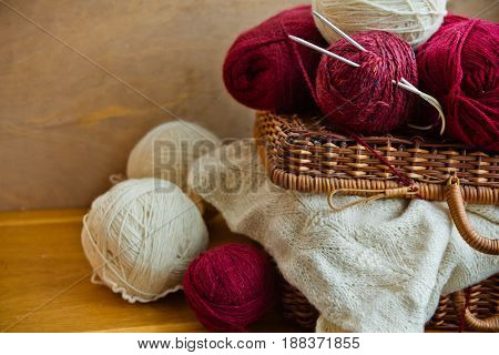 Vintage wicker basket balls clews of red white wool yarn piece of knitted needlework on wood table knitting crafts hobby concept close up