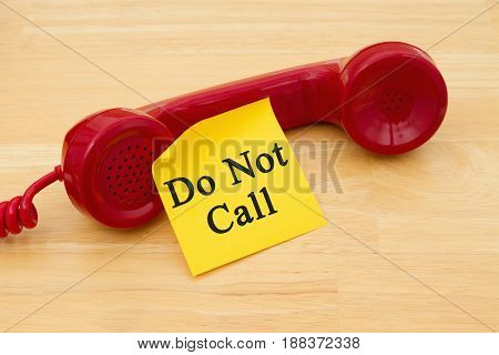 Getting on the do not call list Retro red phone handset with a yellow sticky note and text Do not call