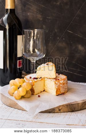 French munster cheese with orange rind red pepper corns white grapes cut off slice wine bottle and glass authentic rustic style