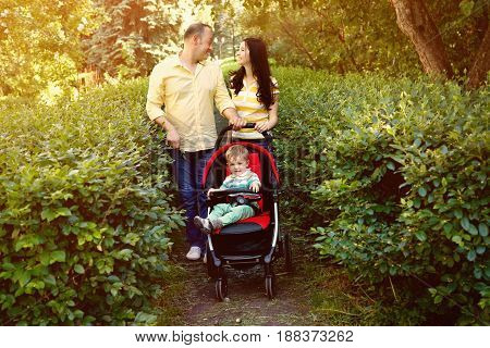 outdoor portrait of a family with baby in stroller. young parents with a baby in pram for a walk in the summer park. Mom, dad and child
