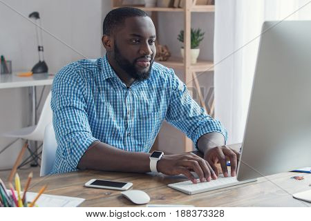 Young african male working in the office business using digital device