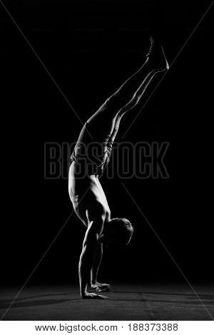 Fitness training. Male athlete walking on his hands or standing upside down in dark gym.