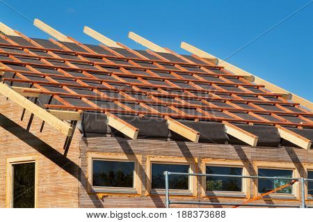 Construction of a wooden roof in an ecological house. External work on the building envelope. The wooden structure of the house near the forest