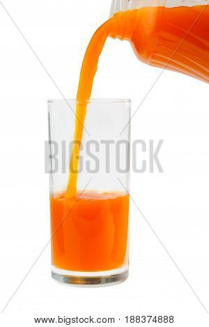 Carrot juice is poured into a glass from the bottle.