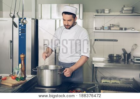 Male japanese restaurant chef cooking in the kitchen boil ingredients