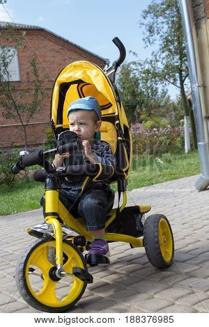 boy sitting on a bicycle and tricycle holding a car