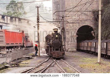 Steam narrow-gauge locomotive stands by the coal loading point. Sichuan province. Yuejin. China.
