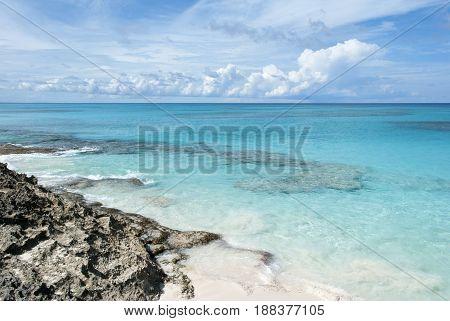 The transparent waters along rocky coastline of uninhabited island Hal Moon Cay (Bahamas).