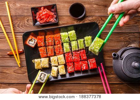 Sushi Set rolls with soy sauce served on black plate on wooden background