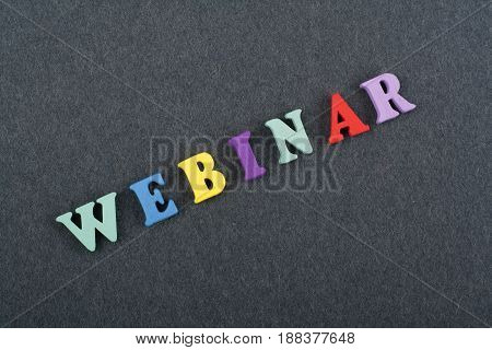 WEBINAR word on black board background composed from colorful abc alphabet block wooden letters, copy space for ad text. Learning english concept