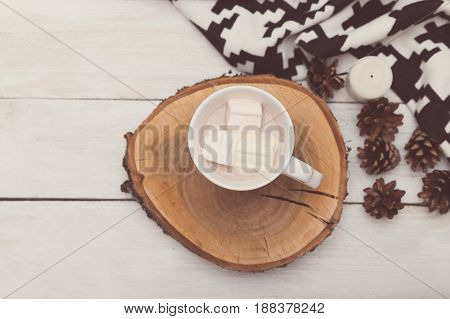 A white sash with cocoa stands on a wooden tray. View from above