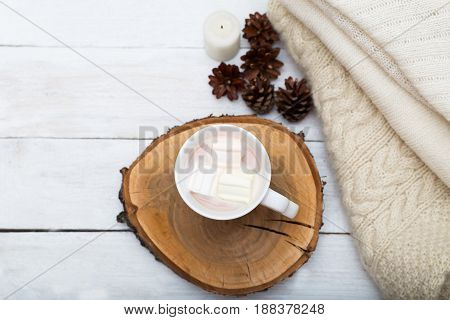 Cup with hot chocolate marshmallows and a stack of knitted things on a white wooden background