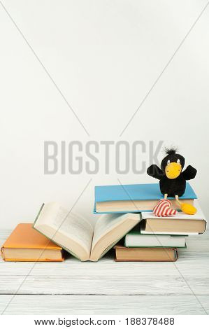 Open book, hardback colorful books on wooden table. Toy crow. Back to school. Copy space for text. Education business concept